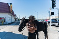 Kenneth stands on the corner with his horse 29
