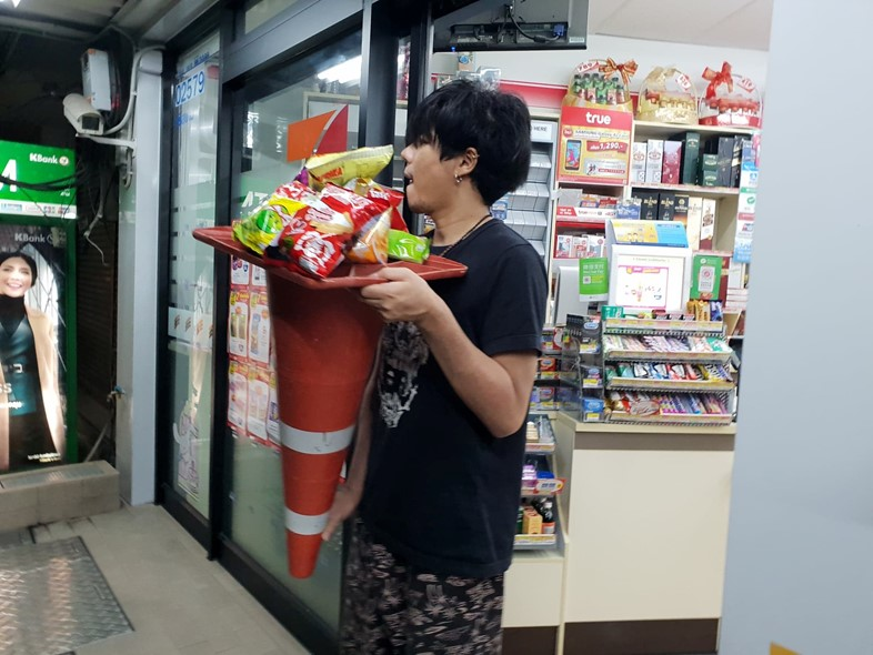 Carrying shopping in traffic cone, Thailand
